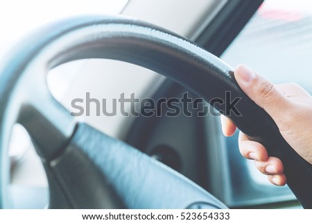 Hand holding on black steering wheel while driving in the car #523654333