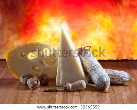 Cheese and salami on a wooden surface with colored background #52365559