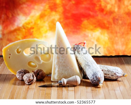 Cheese and salami on a wooden surface with colored background #52365577