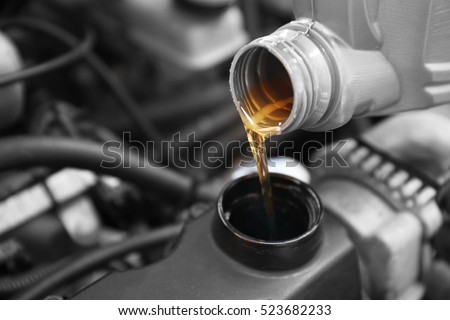 Pouring oil to car engine, close up Royalty-Free Stock Photo #523682233