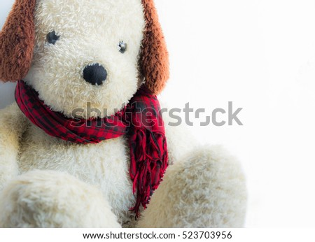 Stuffed dog tied red plaid scarf.