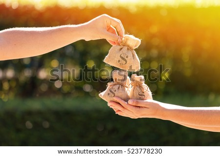 A man and a women hands hold a money bags in the public park for loans to planned investment in the future concept.