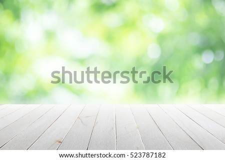 Empty wooden table with blurred city park on background Royalty-Free Stock Photo #523787182