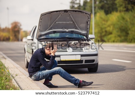 A young man in despair clutched his head, because his car broke down on the road and it is not possible to repair it. #523797412