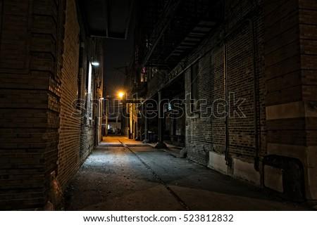 Dark urban city alley at night Royalty-Free Stock Photo #523812832