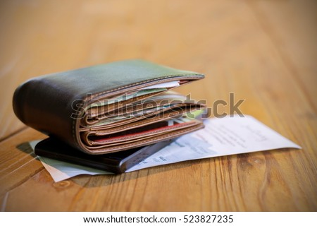 Soft tone of Money and credit card in a leather wallet on wooden table and bill slip background Royalty-Free Stock Photo #523827235