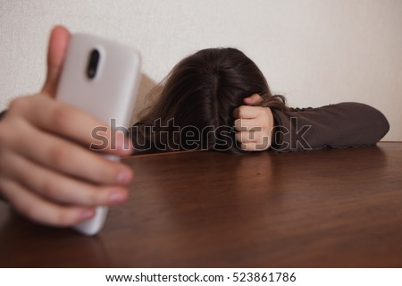 young sad vulnerable girl using mobile phone scared and desperate suffering online abuse cyberbullying being stalked and harassed in teenager cyber bullying concept #523861786