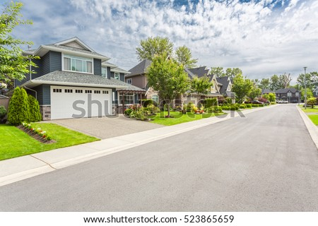Nicely trimmed and manicured garden in front of a luxury house on a sunny summer day. Street of houses in the suburbs of Canada. Royalty-Free Stock Photo #523865659