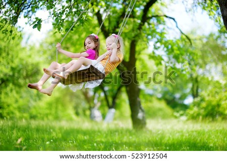 Two cute little sisters having fun on a swing together in beautiful summer garden on warm and sunny day outdoors  #523912504