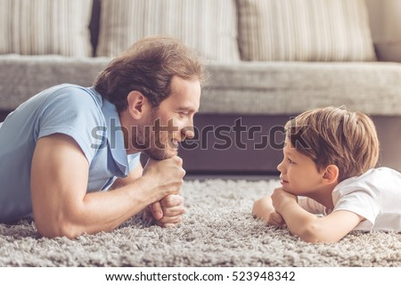Side view of handsome father and his cute son looking at each other and smiling while spending time together at home Royalty-Free Stock Photo #523948342