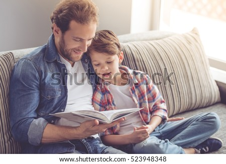 Father and son are reading a book and smiling while spending time together at home #523948348