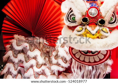 Chinese lion dance for Chinese new year with red fan in the background Royalty-Free Stock Photo #524018977
