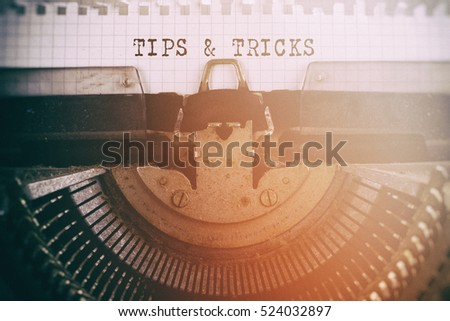 Old typewriter with text TIPS & TRICKS. Retro filtered.