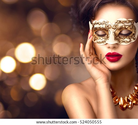 Beauty model woman wearing venetian masquerade carnival mask at party over holiday dark background with magic glow. Christmas and New Year celebration. Glamour lady with perfect make up and hairstyle #524050555
