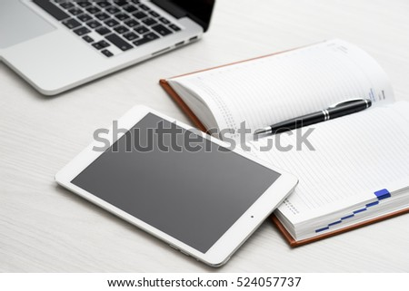 Tablet computer on desk in office with a notepad and a laptop #524057737