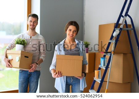 Happy young couple unpacking or packing boxes and moving into a new home #524062954