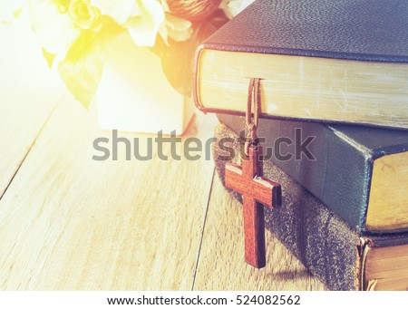 the wooden cross hang on stack of old holy bible with retro vintage color effect
