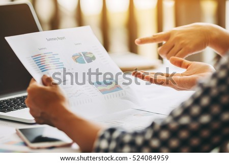 Two business woman investment consultant analyzing company annual financial report balance sheet statement working with documents graphs. Concept picture of economy, market, office,money and tax. #524084959