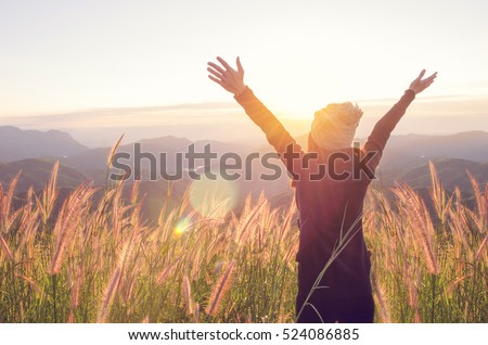 Carefree Happy Woman Enjoying Nature on grass meadow on top of mountain cliff with sunrise. Beauty Girl Outdoor. Freedom concept. Len flare effect. Sunbeams. Enjoyment. Royalty-Free Stock Photo #524086885