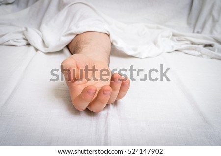 The dead man's body under white cloth with focus on hand in a morgue Royalty-Free Stock Photo #524147902