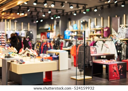 Blurred showcases fashion boutique with sportswear. Blurred big sales on Black Friday. On sale at a clothing store in a modern shopping mall  beautiful lobby at the malls. Big sales.                  Royalty-Free Stock Photo #524159932
