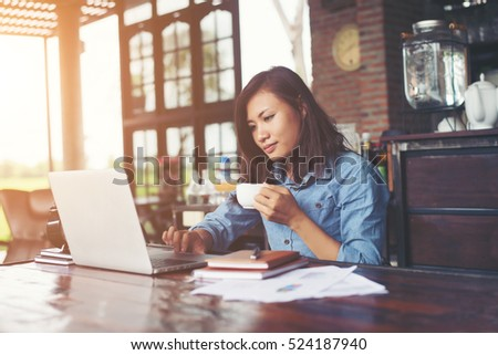 Beautiful hipster woman using laptop at cafe while drinking coffee, Relaxing holiday concept. #524187940