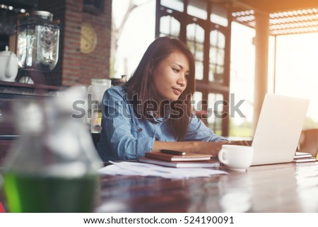 Beautiful hipster woman using laptop at cafe while drinking coffee, Relaxing holiday concept. #524190091