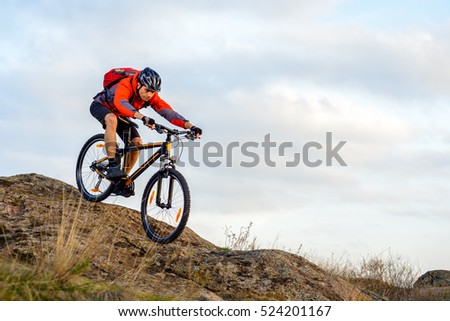 Cyclist in Red Jacket Riding the Bike Down Rocky Hill. Extreme Sport Concept. Space for Text. #524201167