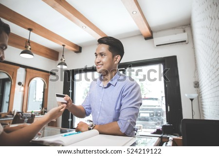 portrait of a man paying using credit card in barbershop