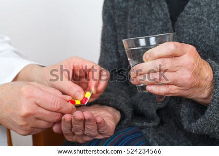 Close up picture of a doctor hand giving pills to a senior woman #524234566