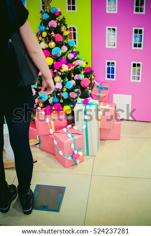 girl looks in black on colorful acid decorations on Christmas tree presents underneath. knitted woolen balls of pink and green color decorated with an artificial tree in nursery.  #524237281