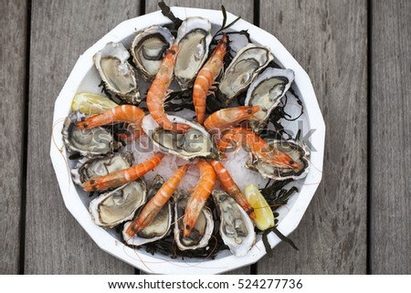 Plate with seafood - oysters and shrimps on wooden background. Toned with sepia colors. Seafood concept.  #524277736