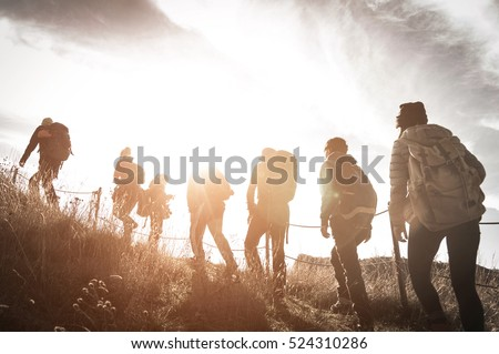 Group of hikers walking on a mountain at sunset #524310286