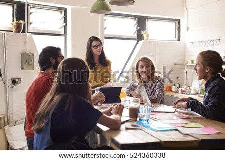 Female Manager Leads Meeting Around Table In Design Office #524360338