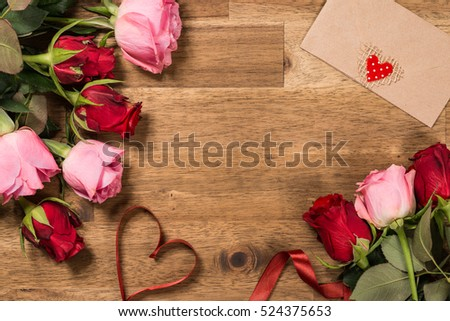 Roses  and red ribbon on wooden background. Valentines day background #524375653