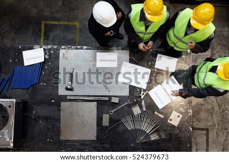 Workers and manager in safety helmets working with documents at factory #524379673