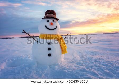 snowman on orange sunset background Royalty-Free Stock Photo #524398663