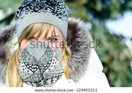 Beautiful young blonde girl in hat and mittens covers his face outside in the cold