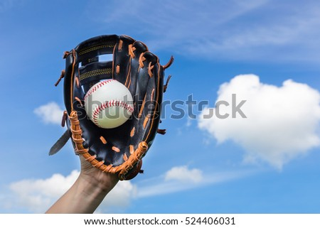 Hand holding baseball in glove with blue sky Royalty-Free Stock Photo #524406031