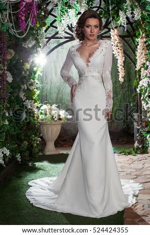 Beautiful bride in the garden. Elegant wedding dress. Bridal wedding dress the bride in the garden. Long wedding dress. Magnificent wedding dress. Luxury bride #524424355