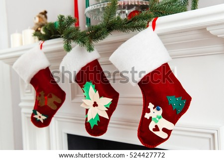 A close picture of beautifully decorated bright red Christmas socks hanging on a fireplace waiting for presents.