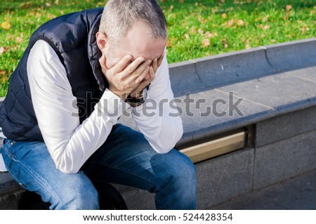Businessman in depression with hands on forehead. stressed young business man, resting face, isolated background of trees outside. Negative human emotion facial expression feelings. Royalty-Free Stock Photo #524428354