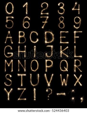 Full english alphabet and numbers set made from burning sparkles on black background. Shiny festive firework latin font. #524436403