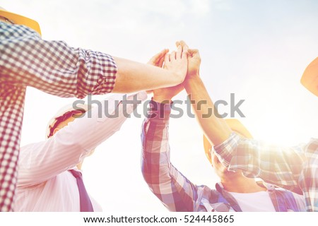 business, building, partnership, gesture and people concept - close up of builders in hardhats making high five outdoors Royalty-Free Stock Photo #524445865