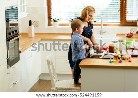 Smart cute child helping mother in kitchen preparing cookies #524491159