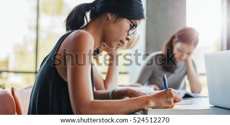 Close up shot of young woman writing notes with classmates studying in background. Students learning in college library.
