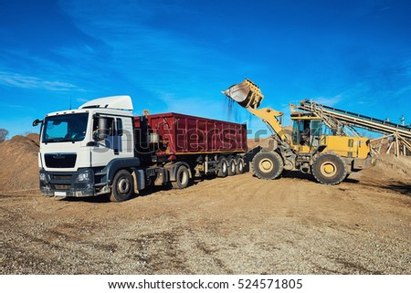 Loading gravel into a truck with a bulldozer. Extraction of gravel. Minerals. Men at work. The sun, blue sky. #524571805