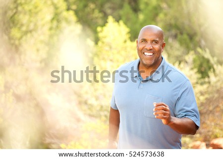 Middle Aged Man Jogging In Park #524573638