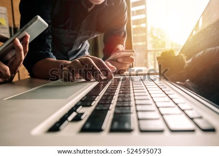 Businessman hand using laptop and tablet with social network diagram and two colleagues discussing data on desk as concept in morning light. Royalty-Free Stock Photo #524595073