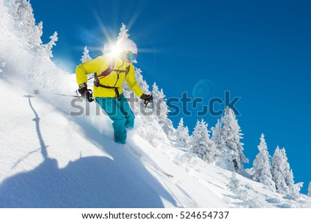 Skier skiing downhill in high mountains during sunny day. #524654737